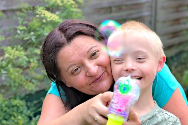 Heureuse mère et fils avec le syndrome de down jouant dans un jardin. Photo Premium