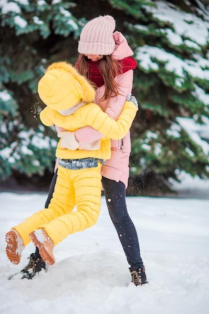 Heureuse mère et son enfant profitent d'un jour de neige en hiver Photo Premium