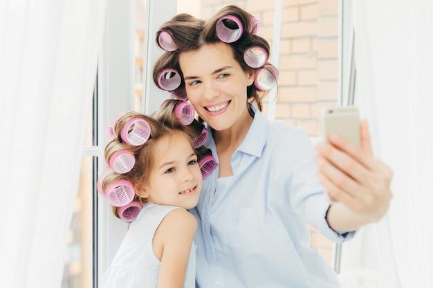 Heureuse mère et son petit enfant avec des bigoudis sur la tête, posent pour faire des selfies, utilisent un téléphone intelligent moderne Photo Premium