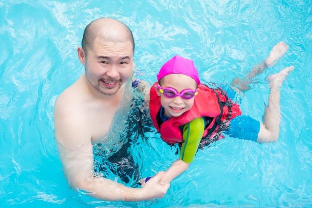 Heureuse petite fille asiatique apprend à nager avec son père dans la piscine Photo Premium