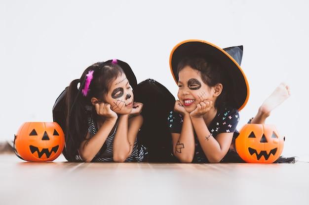 Heureuse petite fille asiatique en costumes et maquillage s'amuser sur la fête d'halloween Photo Premium