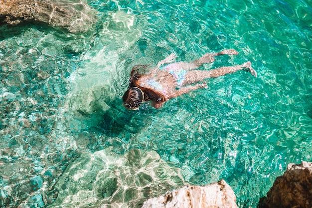 Heureuse petite fille au masque de plongée en apnée plongée sous-marine avec des poissons tropicaux Photo Premium