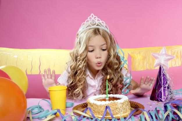 Heureuse petite fille blonde soufflant une bougie de gâteau dans une fête d'anniversaire Photo Premium