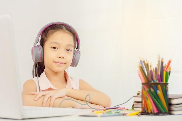 Heureuse petite fille avec des écouteurs et regardant la caméra Photo Premium