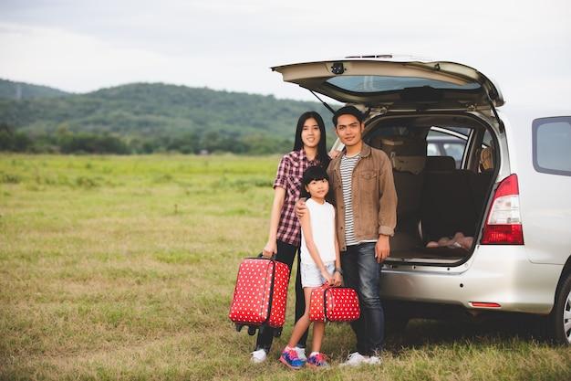 Heureuse petite fille avec la famille asiatique assise dans la voiture Photo Premium