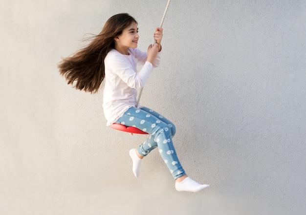 Heureuse petite fille jouant sur une balançoire Photo Premium