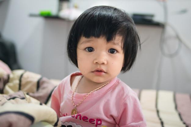Heureuse petite fille jouant sur un lit Photo Premium