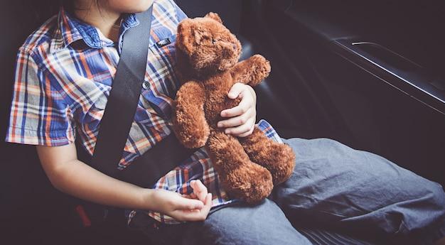 Heureuse petite fille portant la ceinture de sécurité en voiture Photo Premium