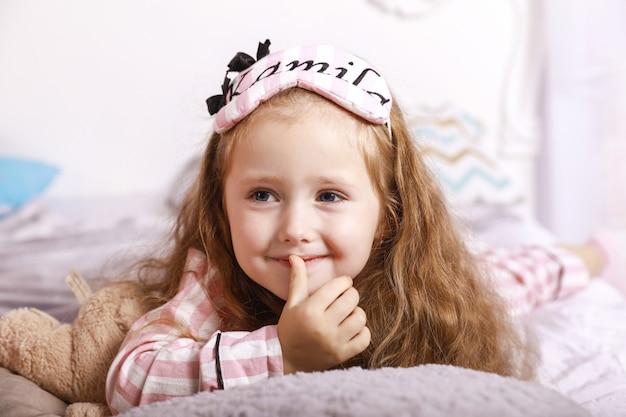 Heureuse Petite Fille Rousse Souriante Est Allongée Sur Les Draps Sur L'énorme Lit Photo gratuit