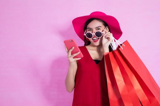Heureuse robe asiatique jolie fille rouge tenant les sacs à provisions et téléphone intelligent à la recherche de suite sur fond rose Photo Premium