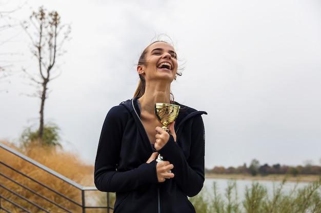 Heureuse sportive jeune femme tenant une coupe du trophée d'or Photo Premium