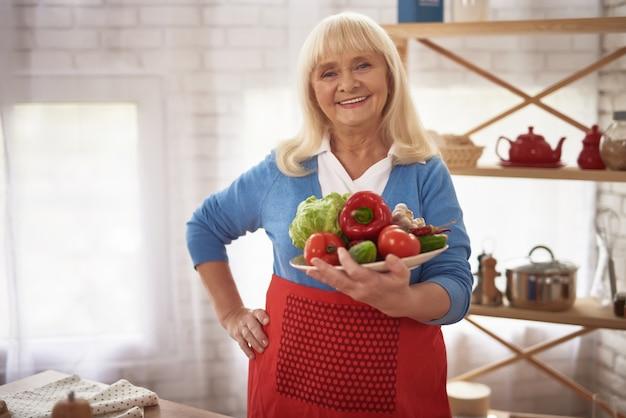Heureuse vieille dame fière de la cuisine peut contenir des légumes. Photo Premium