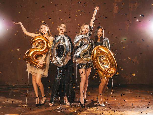 Heureuses Filles Magnifiques Dans Des Robes De Soirée Sexy élégantes Tenant Des Ballons D'or Et D'argent 2020 Photo gratuit
