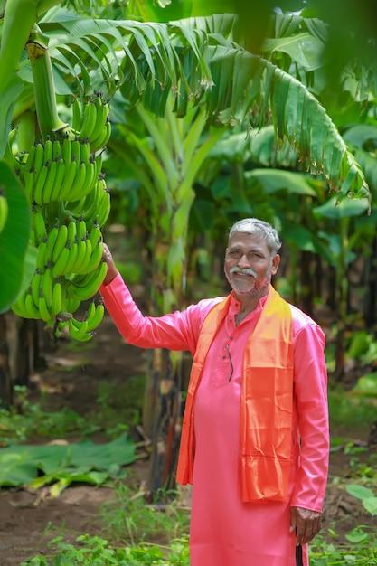 Heureux Agriculteur Indien Tenant Un Bananier Cru Dans La Main Photo Premium
