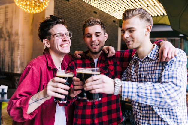 Heureux ami masculin faisant des acclamations avec des verres à bière Photo gratuit