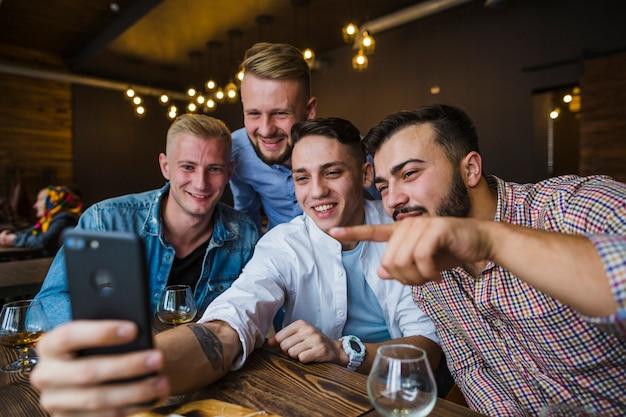 Heureux amis assis au restaurant en prenant selfie Photo gratuit