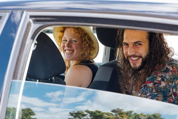 Heureux amis assis dans la voiture lors d'une halte le jour de l'été Photo gratuit