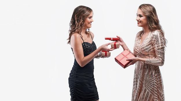 Heureux amis de filles échangeant des cadeaux isolés sur blanc Photo Premium