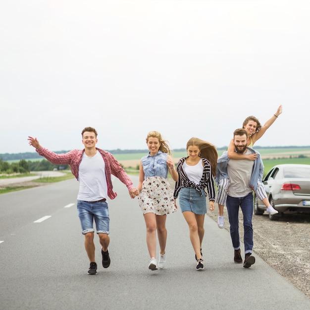 Heureux amis marchant sur la route ensemble se moquer Photo gratuit