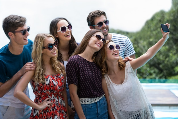 Heureux amis prenant un selfie près de la piscine Photo Premium