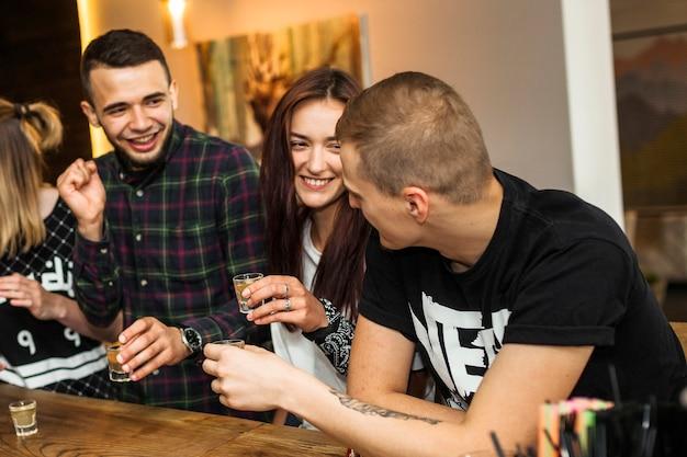 Heureux amis profitant de boire la tequila au bar Photo gratuit