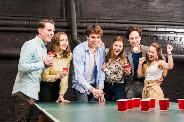 Heureux amis, regarder, balle, tandis que, homme, bière pong bière, table Photo gratuit
