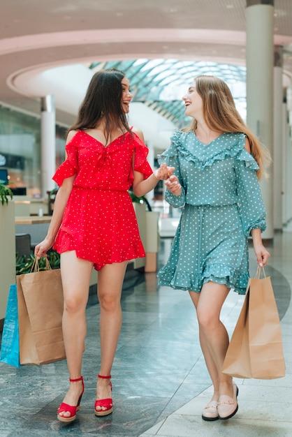 Heureux amis s'amusant au centre commercial Photo gratuit