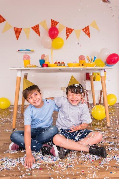 Heureux amis de sexe masculin jouant avec des confettis lors de la fête d'anniversaire Photo gratuit
