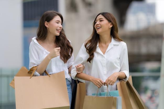 Heureux Amis Shopping, Deux Jeunes Femmes Tiennent Des Sacs à Provisions Photo Premium