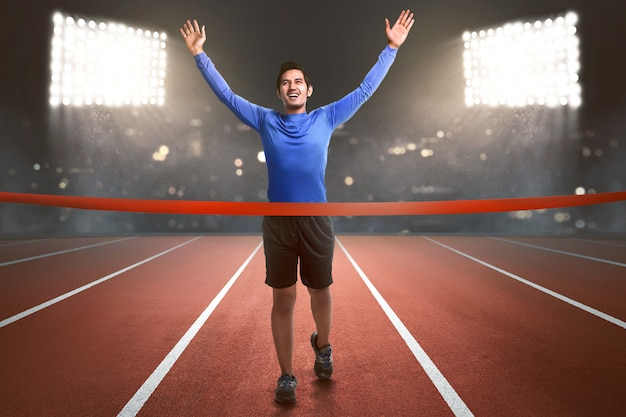 Heureux athlète asiatique homme en cours d'exécution à la ligne d'arrivée Photo Premium