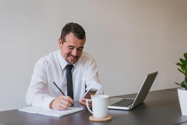 Heureux beau homme d'affaires senior à l'aide d'un smartphone et des notes au bureau. Photo Premium