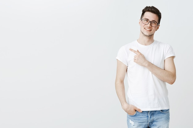 Heureux Beau Jeune étudiant Masculin Dans Des Verres Doigt Pointé à Gauche à Copyspace Photo gratuit