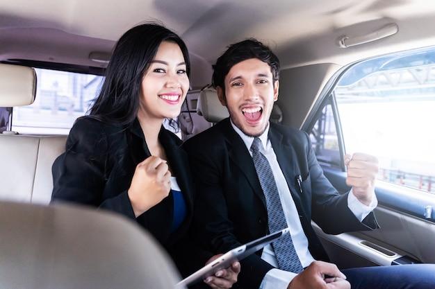 Heureux bel homme d'affaires et femme d'affaires assis dans la voiture de luxe limousine, travaillant sur ordinateur portable, fonctionne à tout moment et n'importe où concept. Photo Premium