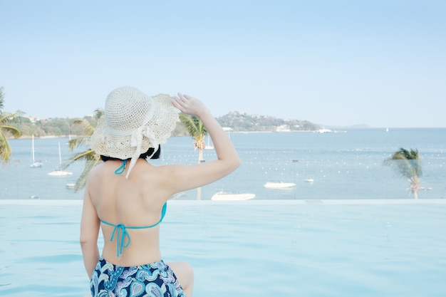 Heureux bikini femme sur la piscine et la mer nuages ciel. Photo Premium