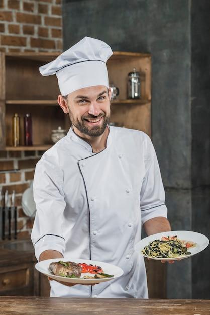 Heureux chef masculin en uniforme blanc offrant des plats délicieux Photo gratuit
