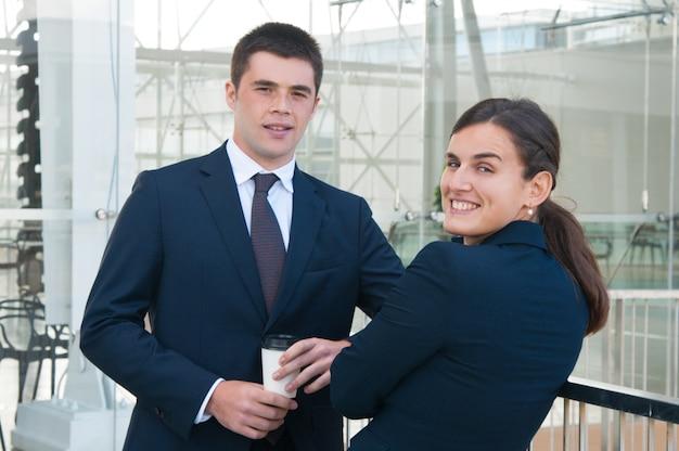 Heureux collègues boire du café et posant à l'extérieur de la caméra Photo gratuit