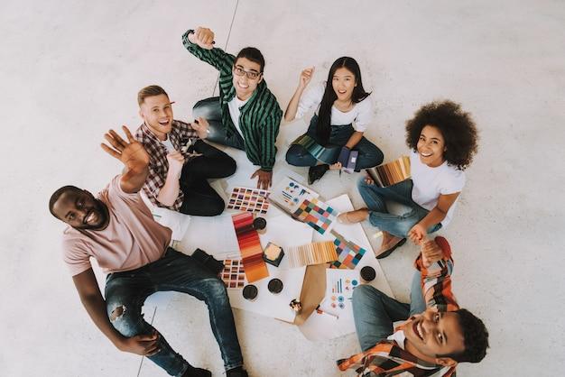Heureux collègues est assis sur le sol et fête Photo Premium