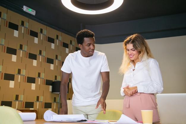 Heureux Concepteur Afro-américain Montrant Le Projet De Client Blonde Photo gratuit