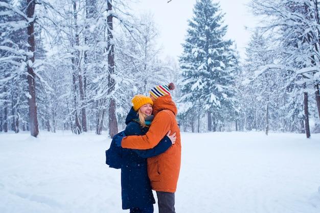 Heureux couple d'amoureux dans la forêt d'hiver enneigé Photo Premium