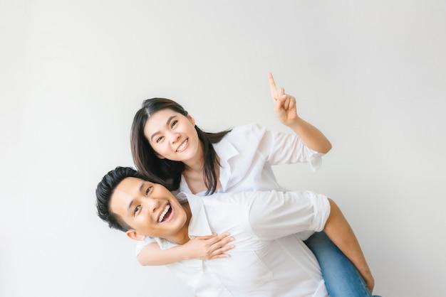 Heureux couple asiatique amoureux s'amusant à cheval Photo Premium