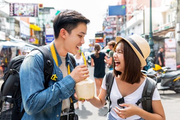 Heureux couple asiatique backpackers touristiques voyageant dans la route de khao san, bangkok Photo Premium