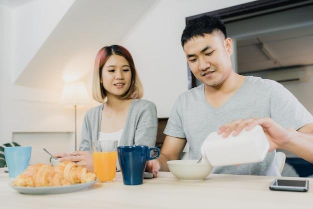 Heureux couple asiatique prenant son petit déjeuner, céréales, lait, pain et boisson au jus d'orange Photo gratuit