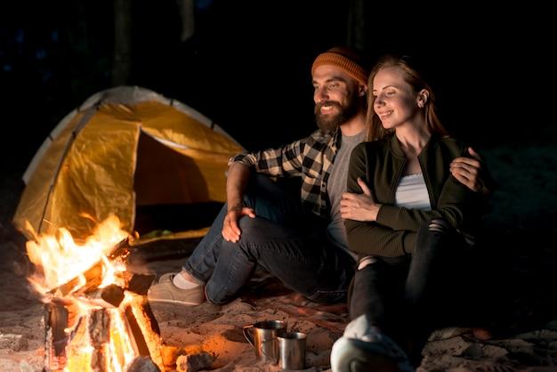 Heureux couple assis ensemble devant un feu de joie Photo gratuit