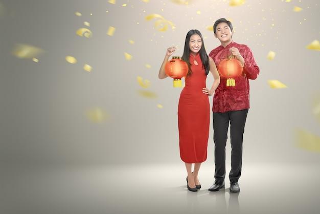 Heureux couple chinois en vêtements cheongsam tenant des lanternes rouges Photo Premium