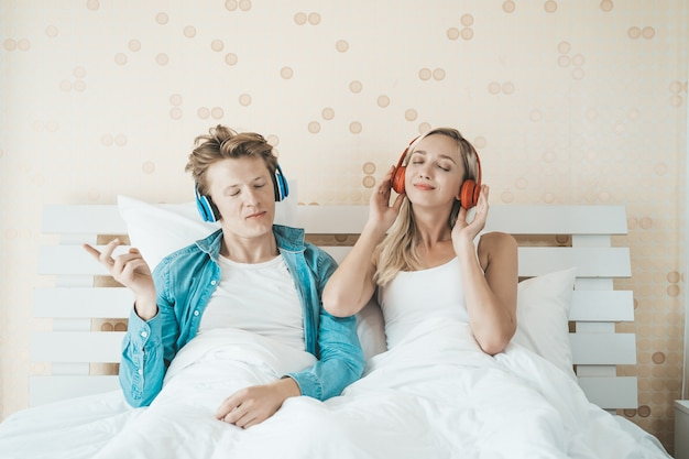 Heureux couple écoute la chanson du matin dans la chambre Photo gratuit