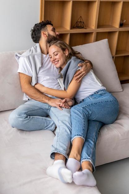 Heureux Couple Embrassé Sur Le Canapé à La Maison Photo gratuit