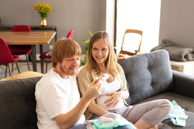 Heureux couple enceinte vérifiant les vêtements de bébé dans le salon Photo gratuit