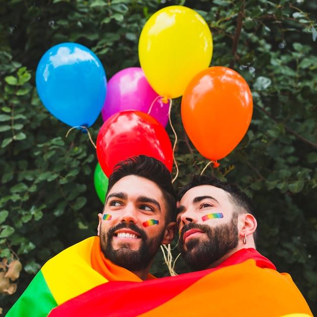 Heureux couple gay avec des ballons lgbt étreignant dans le jardin Photo gratuit