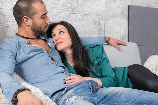 Heureux Couple International D'homme à Barbe Et Sa Femme Brune Assise Dans Une étreinte Sur Le Canapé Dans Le Salon Photo Premium