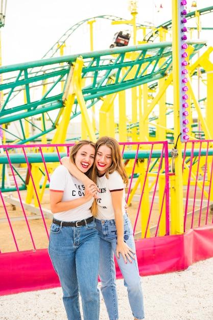 Heureux, couple lesbien, debout, devant, montagnes russes Photo gratuit